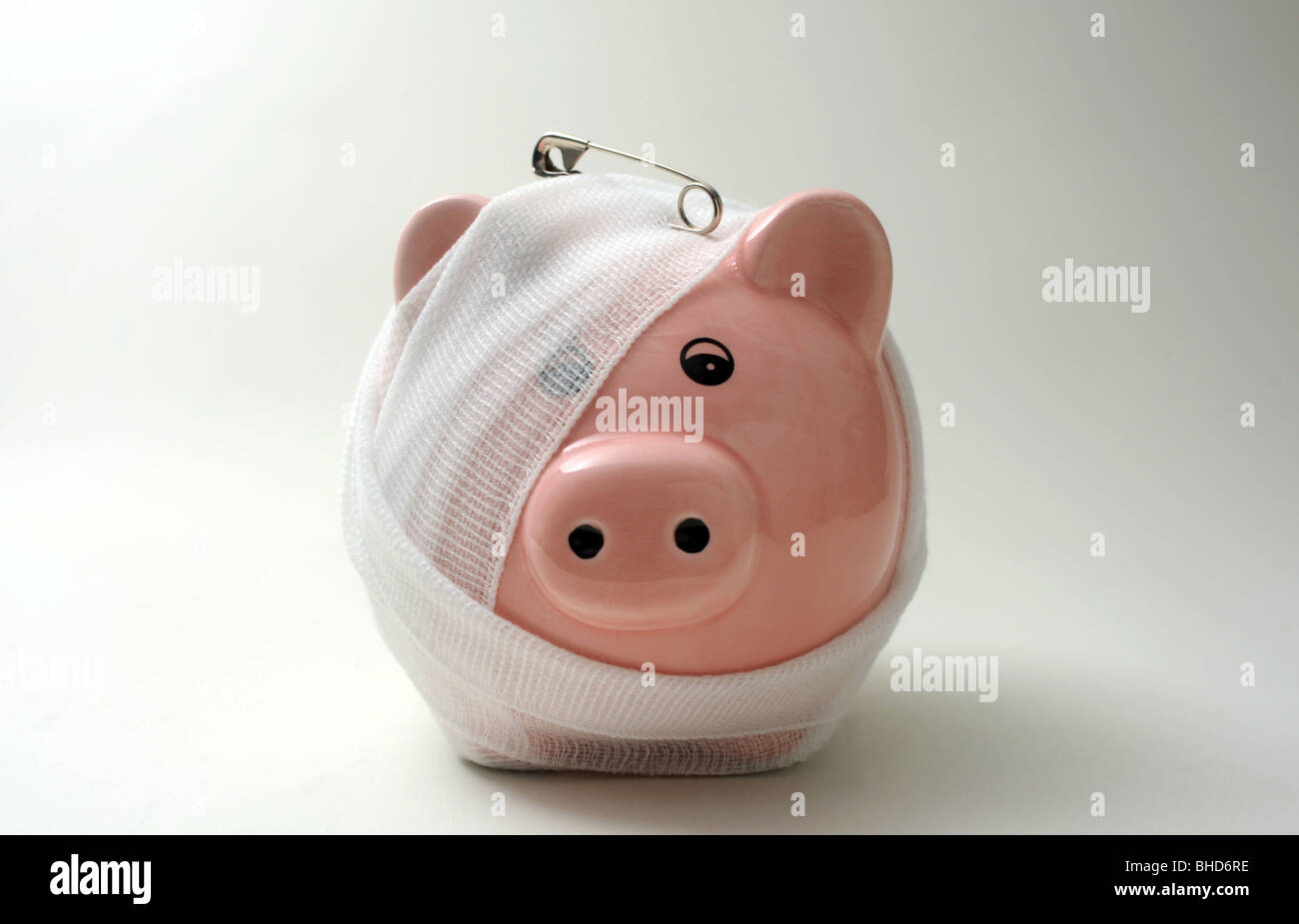 BANDAGED/INJURED PIGGYBANK WITH SAFETY PIN RE FINANCE LOANS CASH MONEY SAVINGS PIGGY BANK BANKS MORTGAGES INCOMES - Stock Image