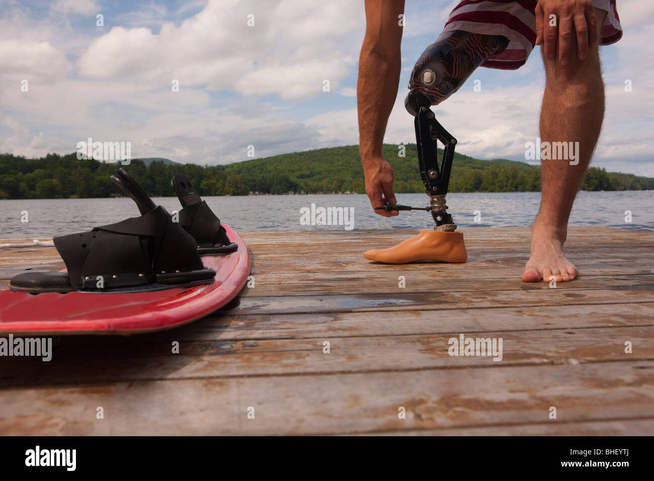 Disabled athlete adjusting his artificial leg on a dock - Stock Image