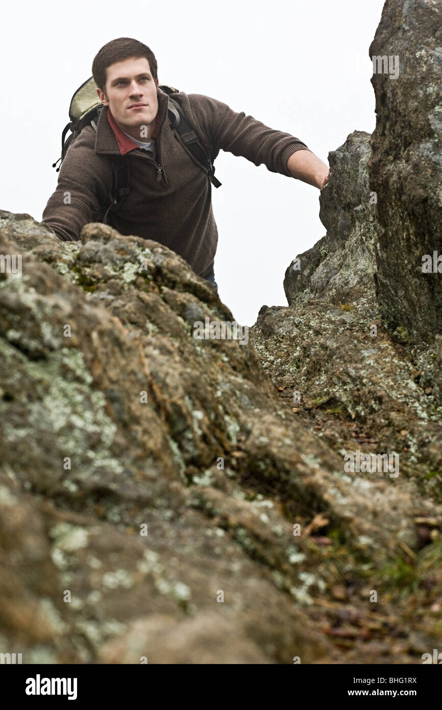 A male hiker emerges from climbing a forest cliff edge - Stock Image