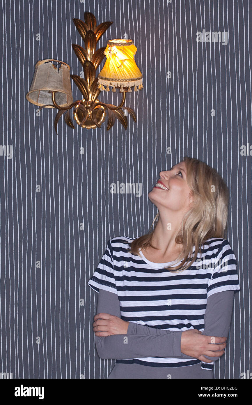 Young woman looking up at wall lamp - Stock Image