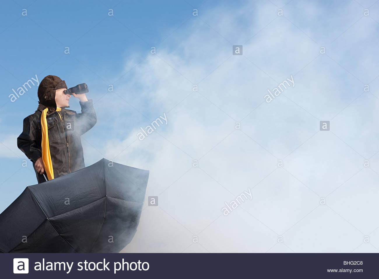 Boy with binoculars and umbrella - Stock Image