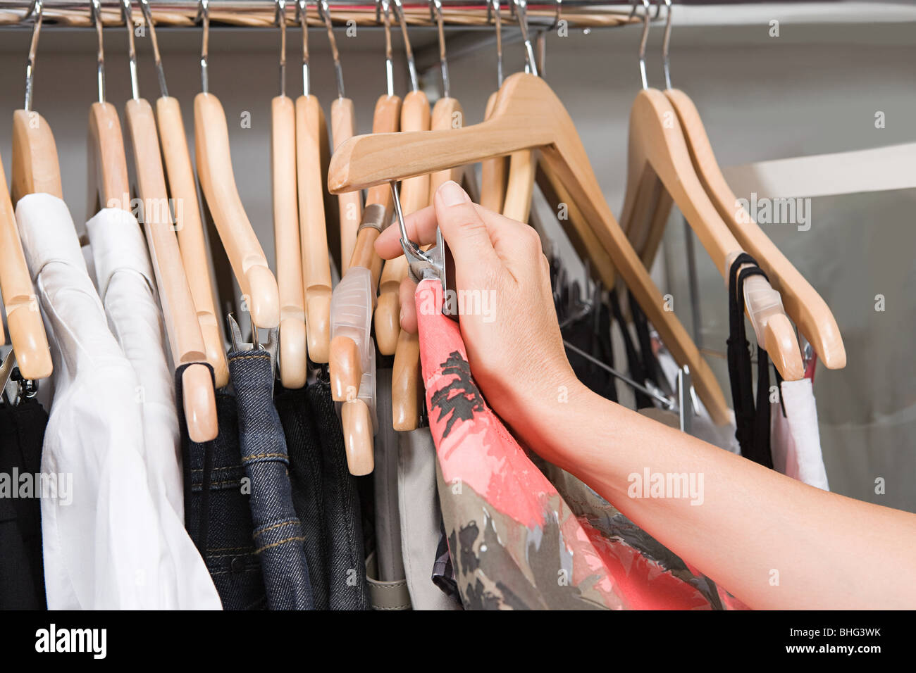 Hand of a woman and clothing rail - Stock Image
