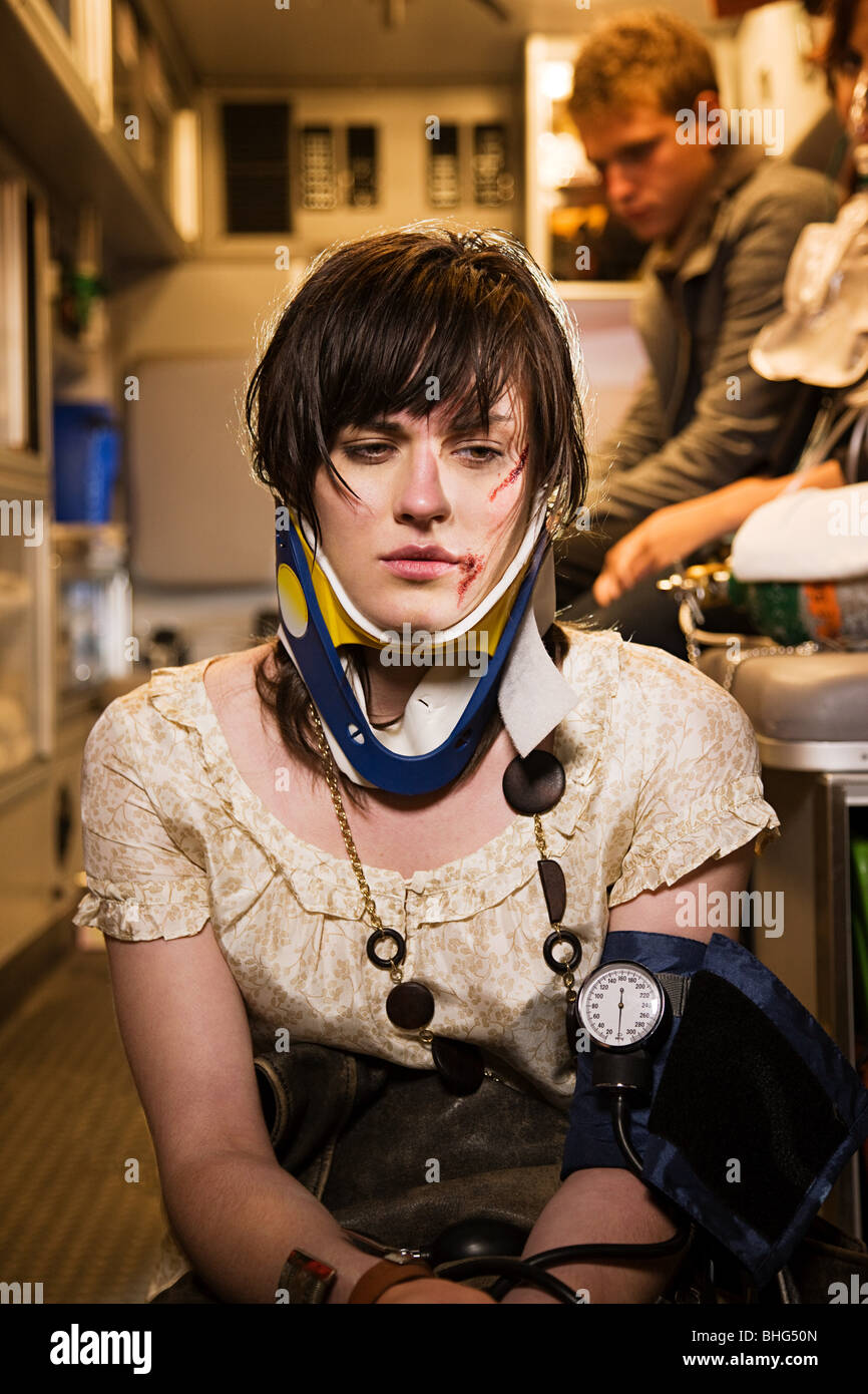 Injured young woman in an ambulance - Stock Image