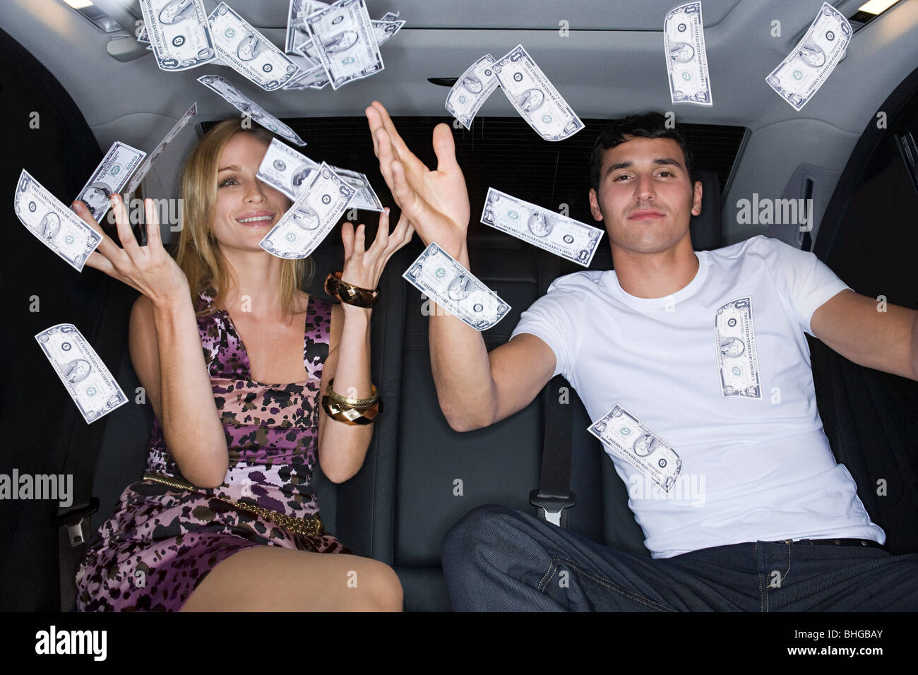 Wealthy couple celebrating in a car - Stock Image