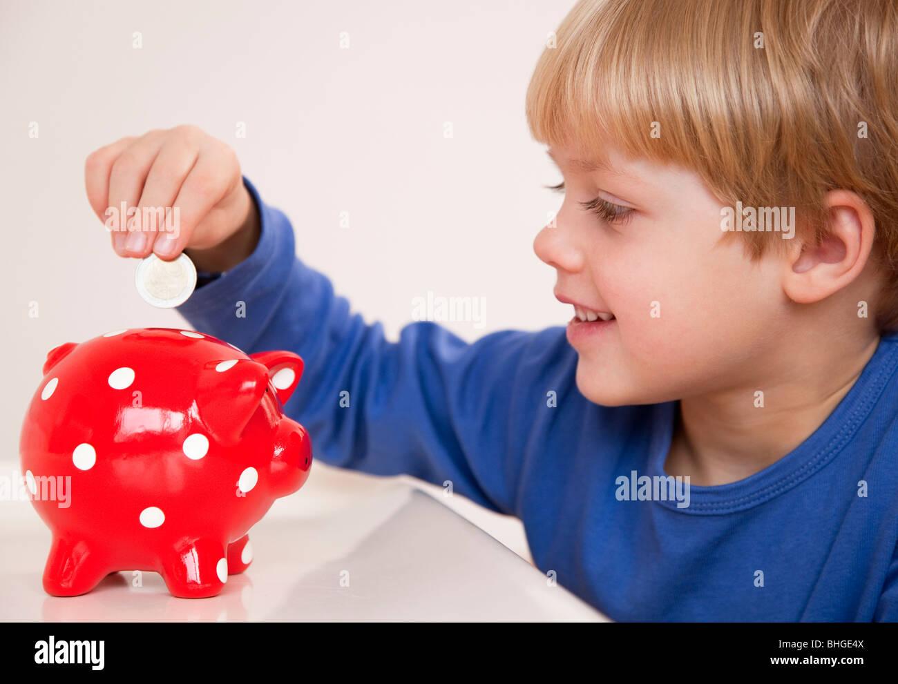 boy saving money - Stock Image