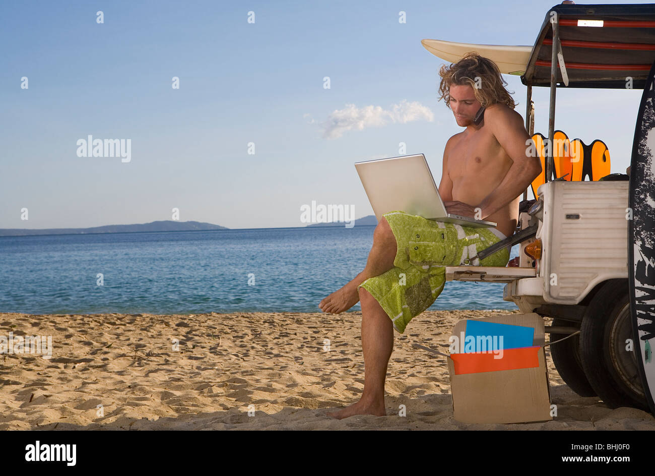 man at beach jeep with laptop, phone - Stock Image
