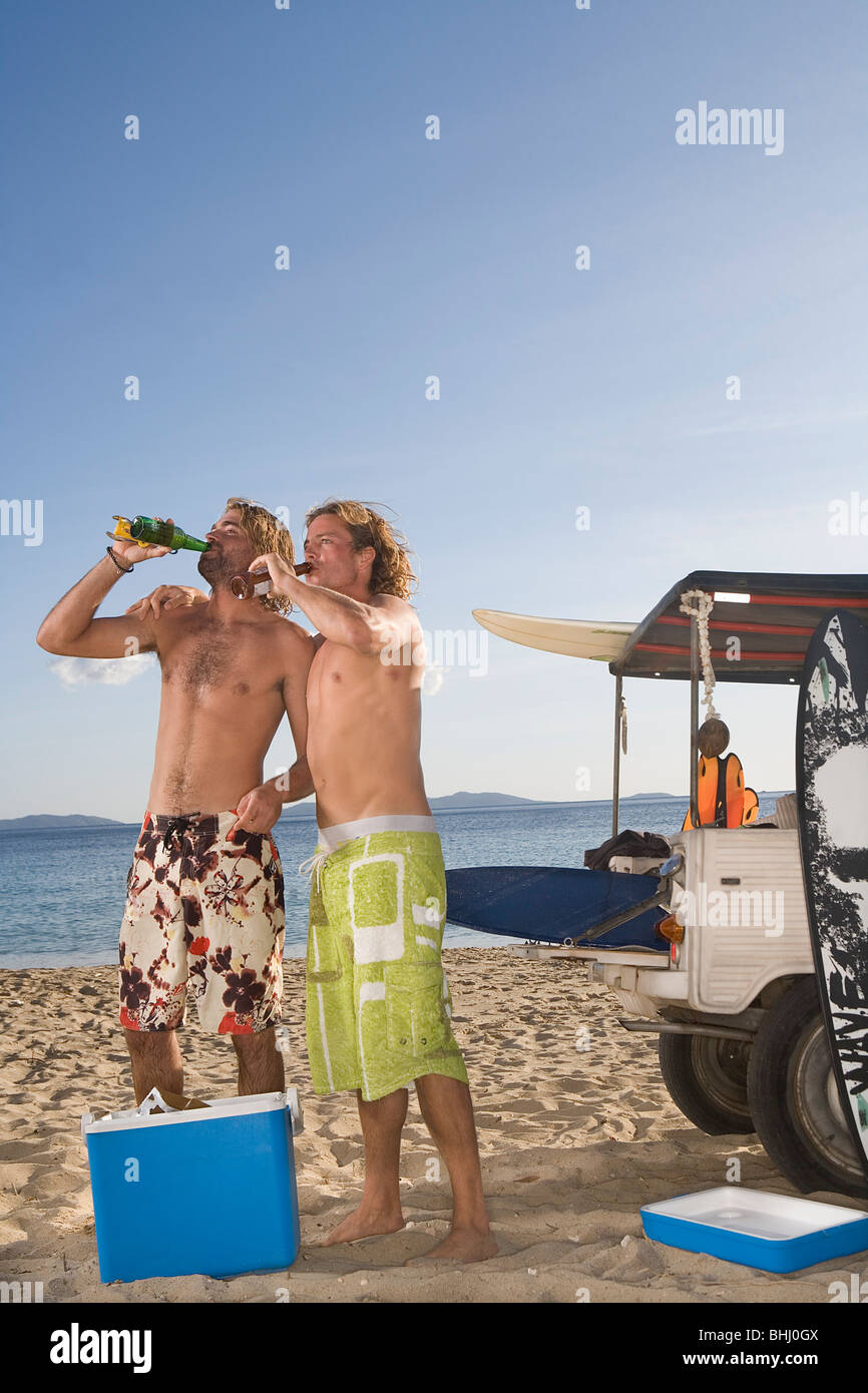 young men at beach drink beer by jeep - Stock Image