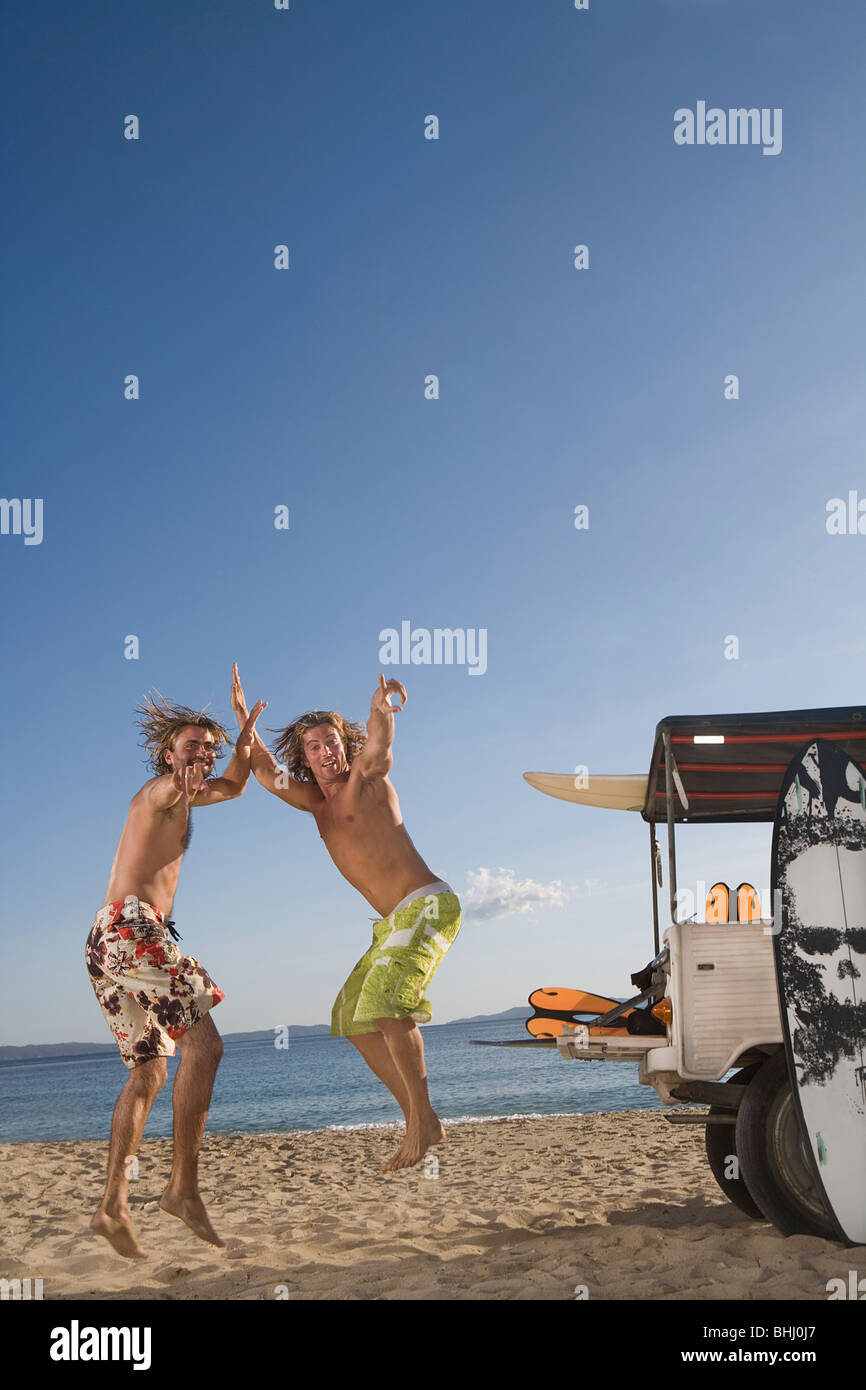 young men jump at beach by jeep - Stock Image