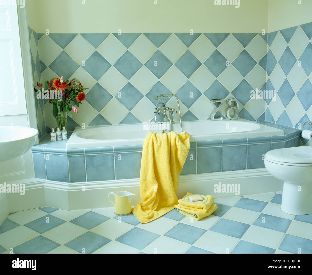Blue+white checker-board tiled wall above bath with blue tiled Stock ...