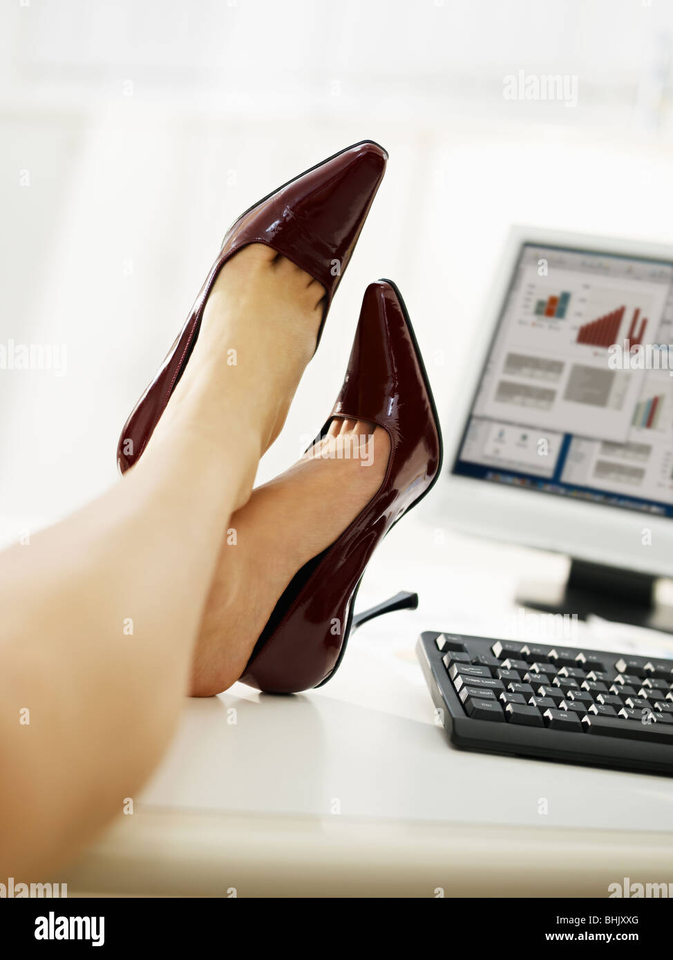 business woman taking off shoes in office. - Stock Image