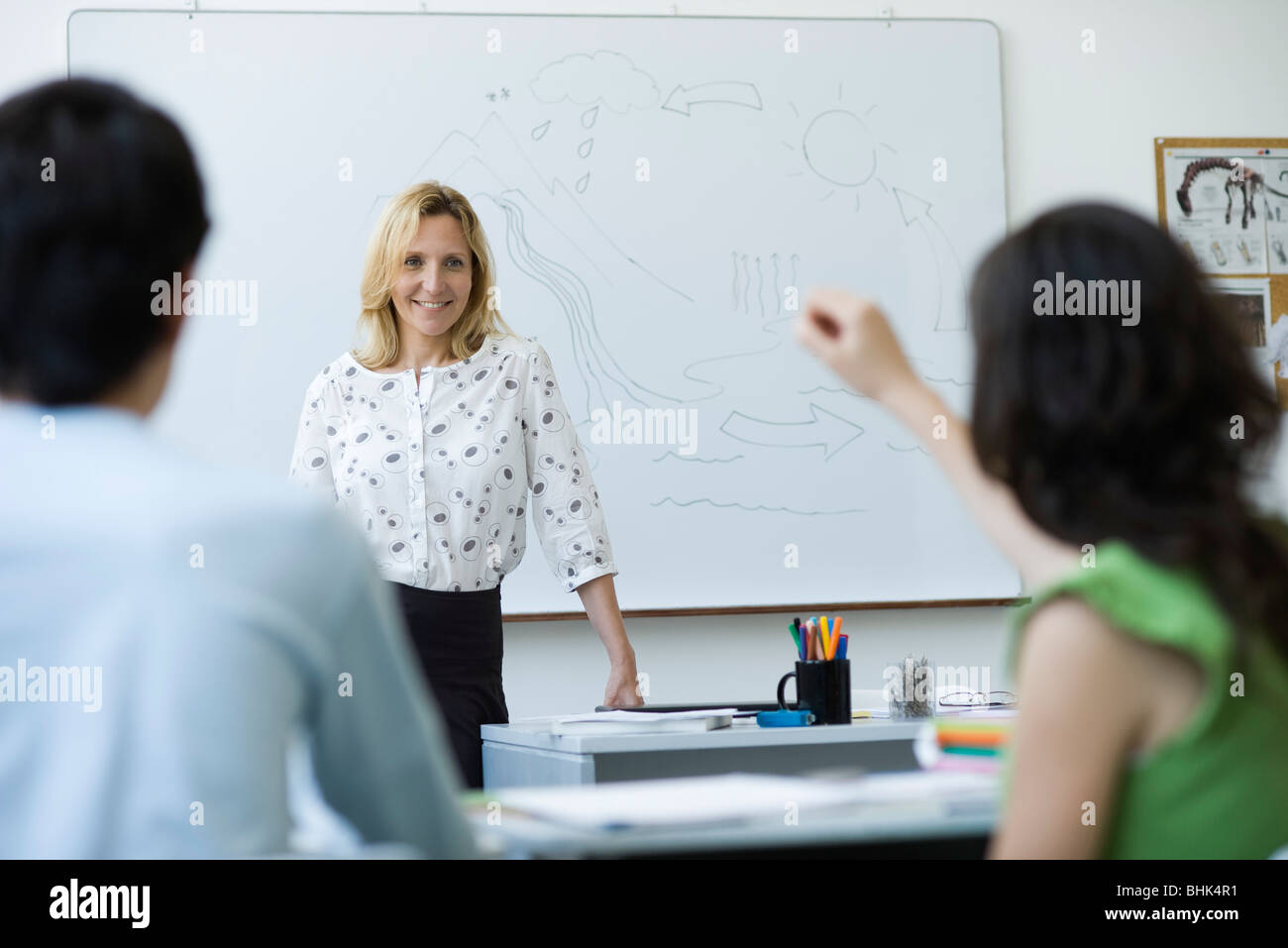 High school teacher standing in front of class, answering question - Stock Image
