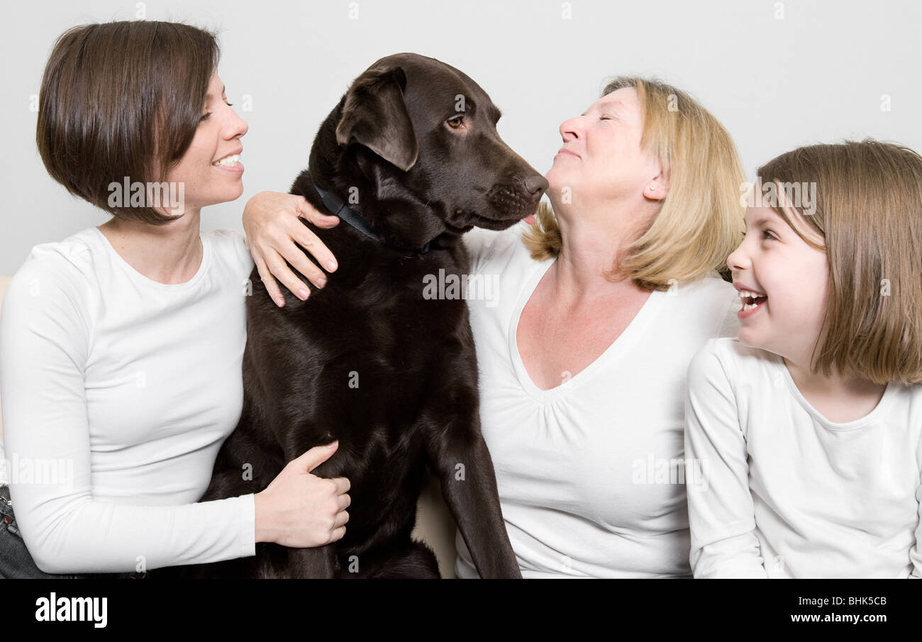 Shot of Three Generations of a Family Laughing with their Dog Stock Photo