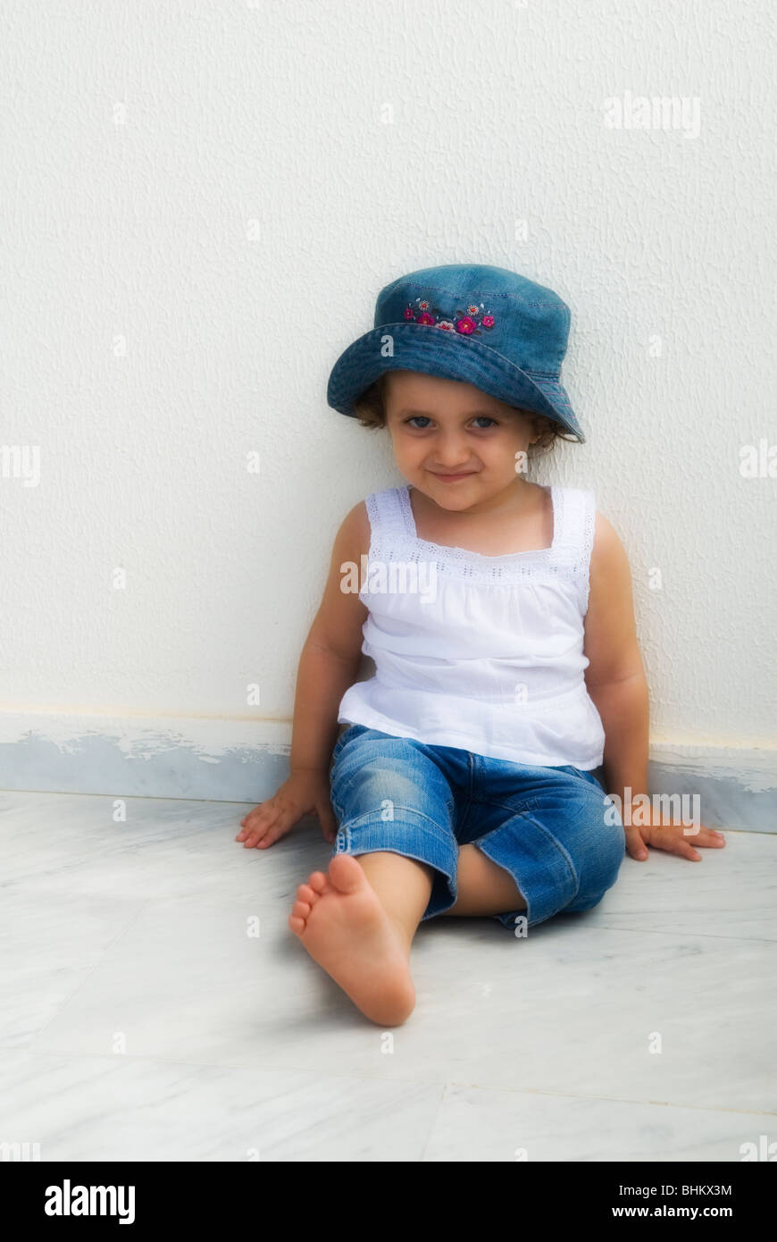 Cute little girl wearing jeans sat on the floor Beirut Lebanon Middle East - Stock Image