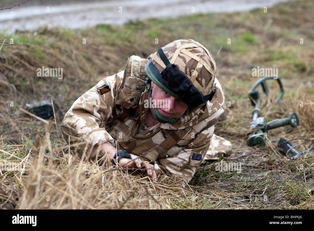 A british soldier uses a metal detector to locate an IED roadside bomb and prepares to destroy it during a training - Stock Image