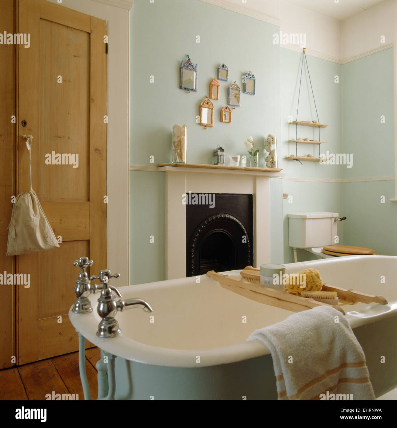 Roll-top bath with wooden bath-rack in pale green bathroom with pine ...