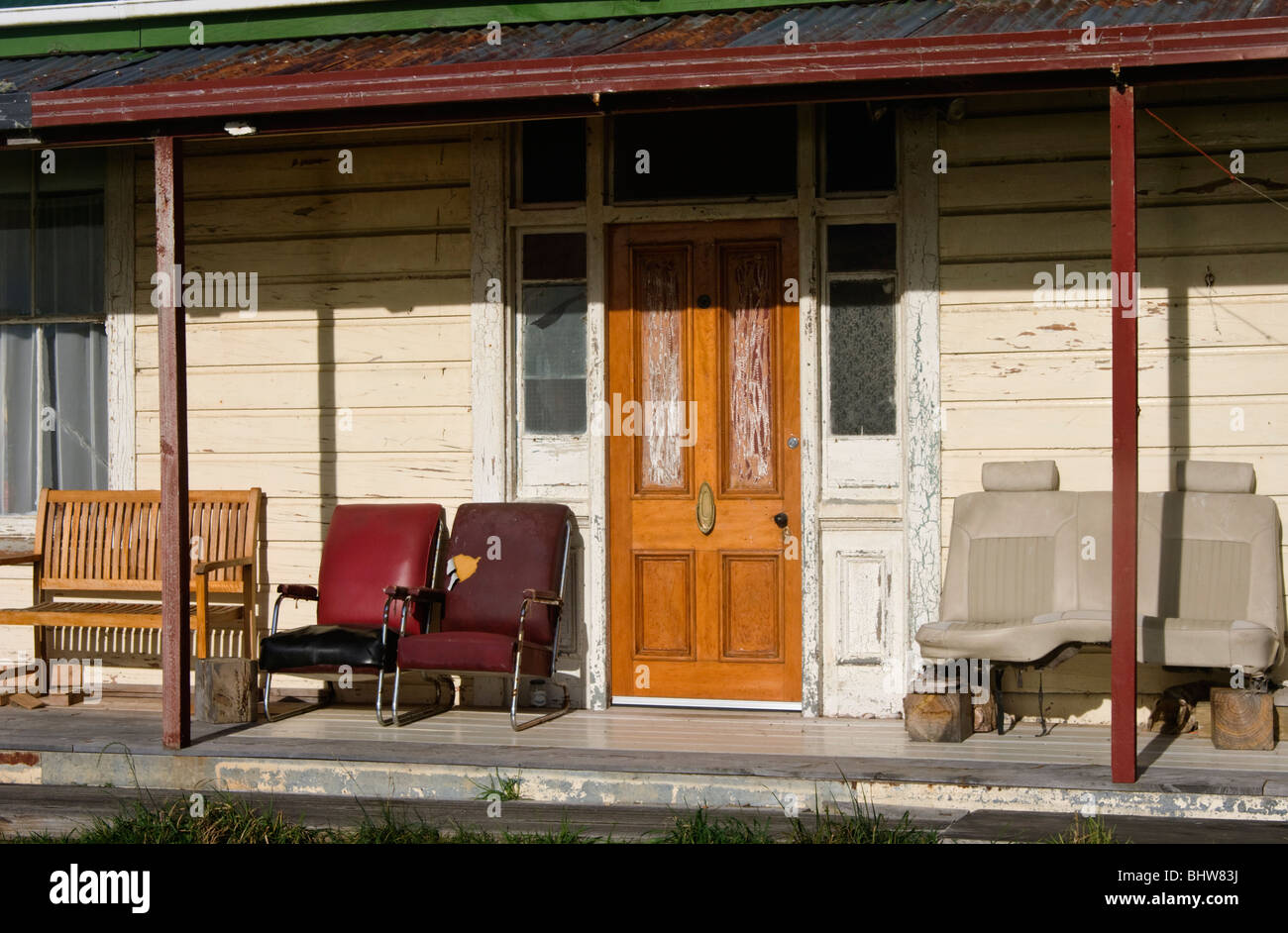 Verandah Of Old House In New Zealand With Various Pieces Of Dilapidated  Seating Including