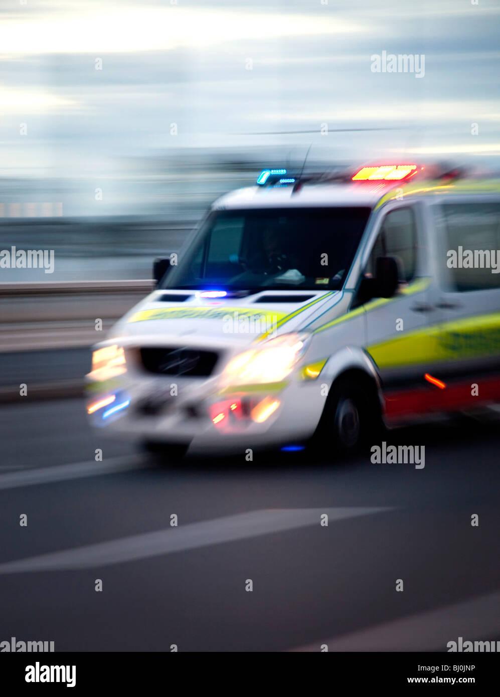 Ambulance motoring along street with lights flashing - Stock Image