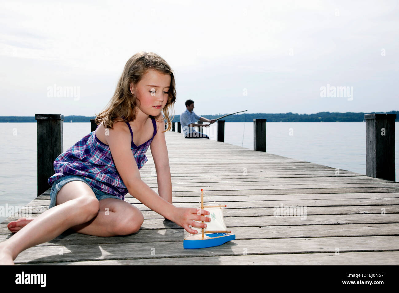 young girl playing with toy boat on pier while father is angling in background - Stock Image