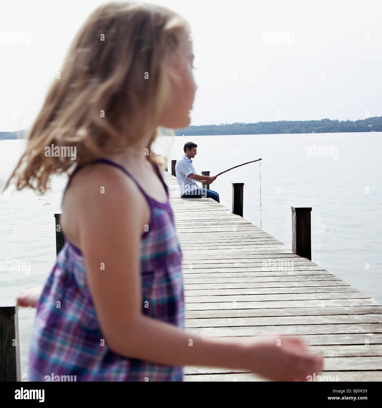 man angling on pier with young daughter in foreground - Stock Image