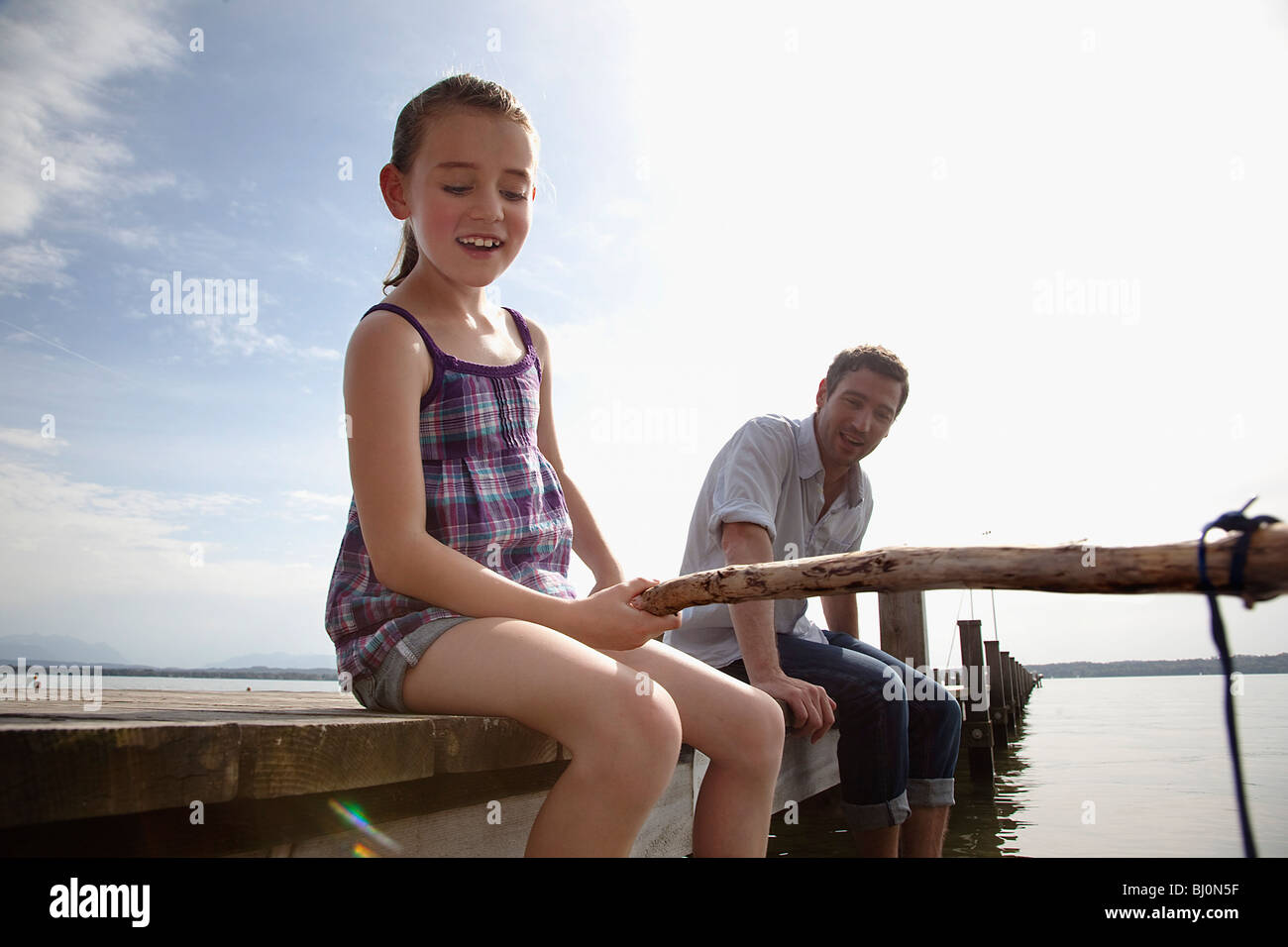 father and daughter on pier angling together - Stock Image