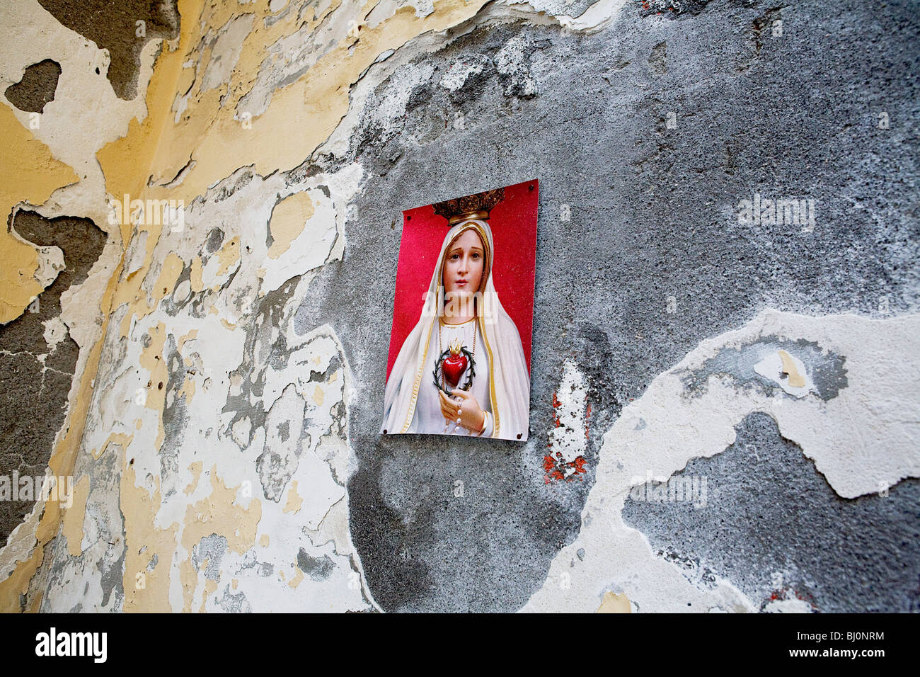 picture of virgin mary hanging on wall in Italy - Stock Image