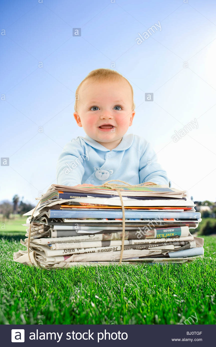 Baby sitting in grass with bundle of newspapers - Stock Image