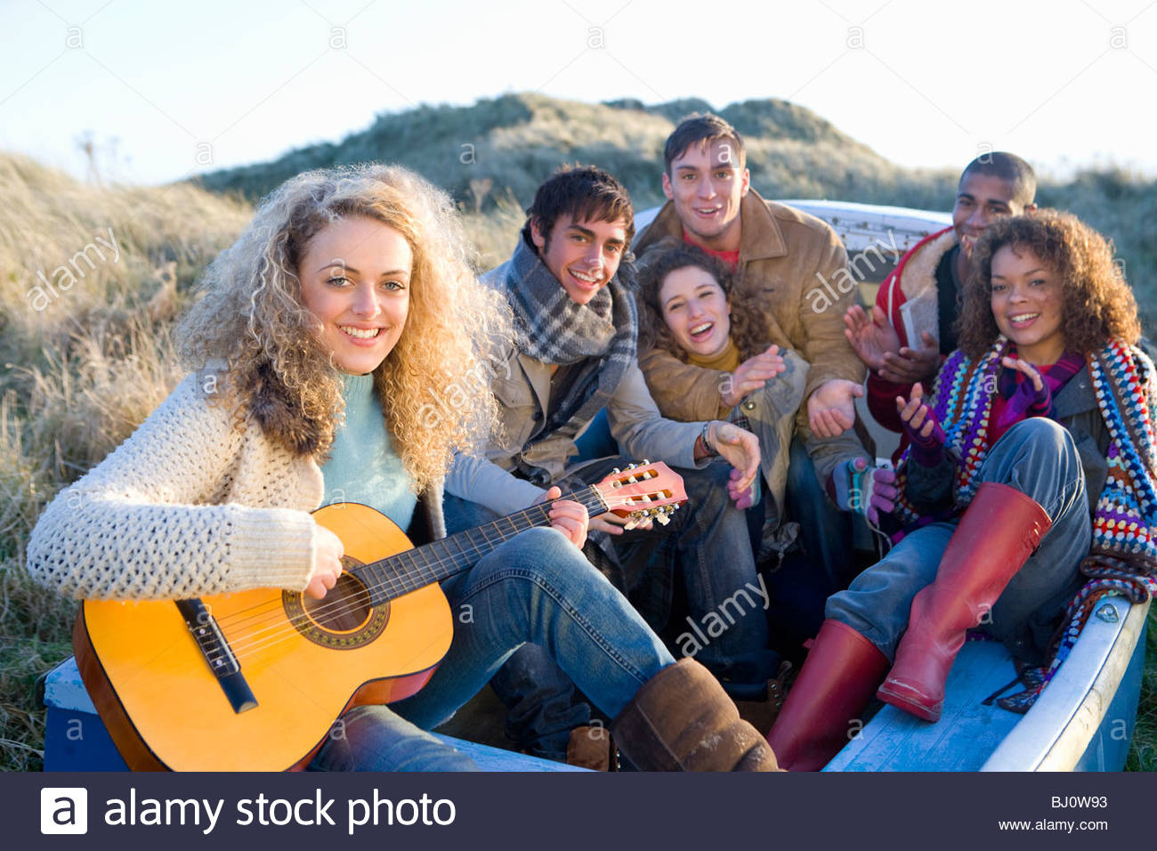 Friends sitting in boat singing and having fun - Stock Image