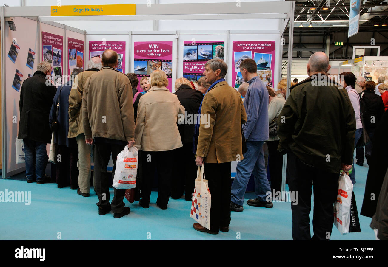 Visitors selecting holidays from SAGA Holidays stand at Destinations the Holiday & Travel Show at the NEC Birmingham - Stock Image