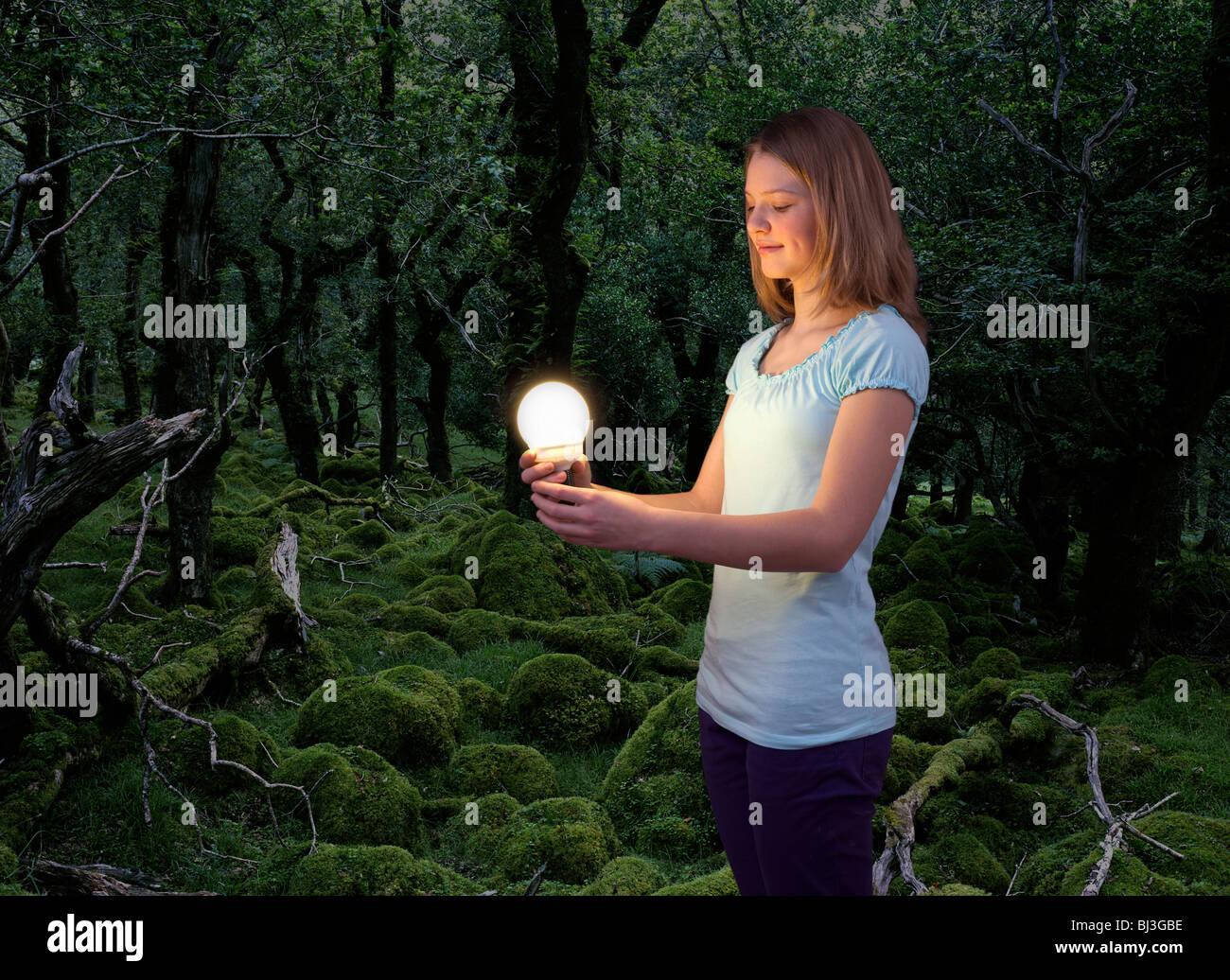 girl with energy saving light bulb - Stock Image