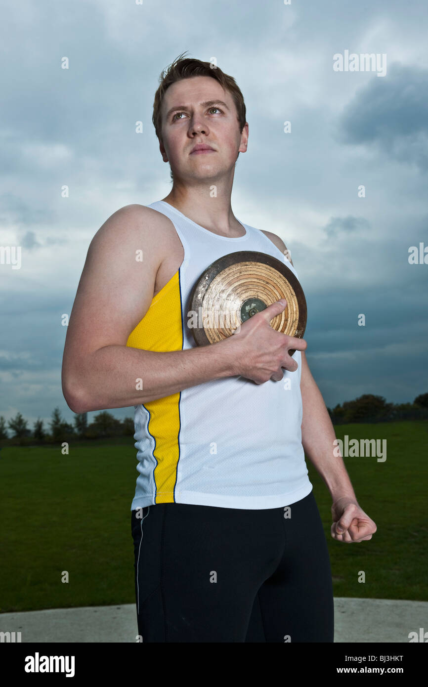 Male athlete posing with discus - Stock Image