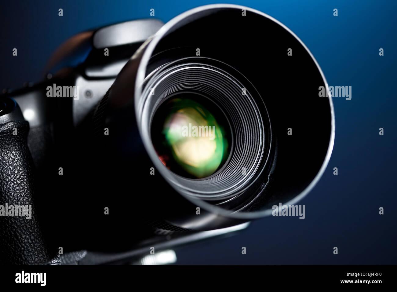 Professional DSLR camera on blue background. - Stock Image