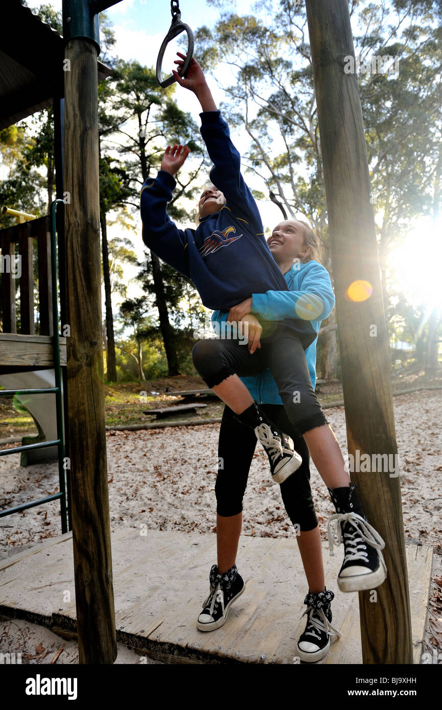 Young child (10 years old) helping younger sister (7 years old) reach a ring on outdoor playground. - Stock Image