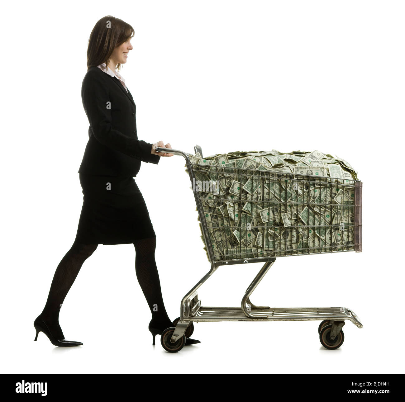 businessperson with a shopping cart full of money - Stock Image