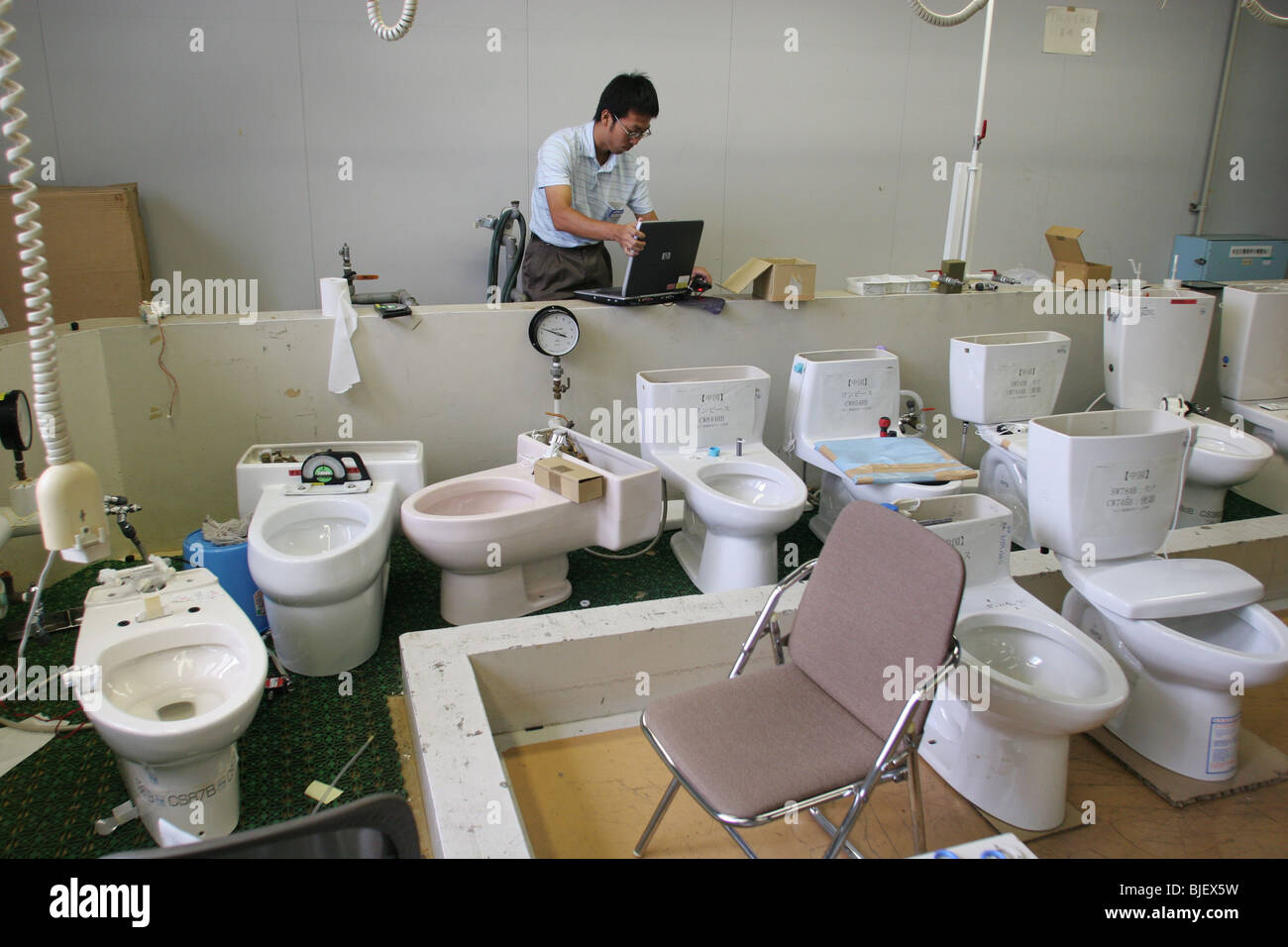 An employee checks the water functions of various types of toilets ...