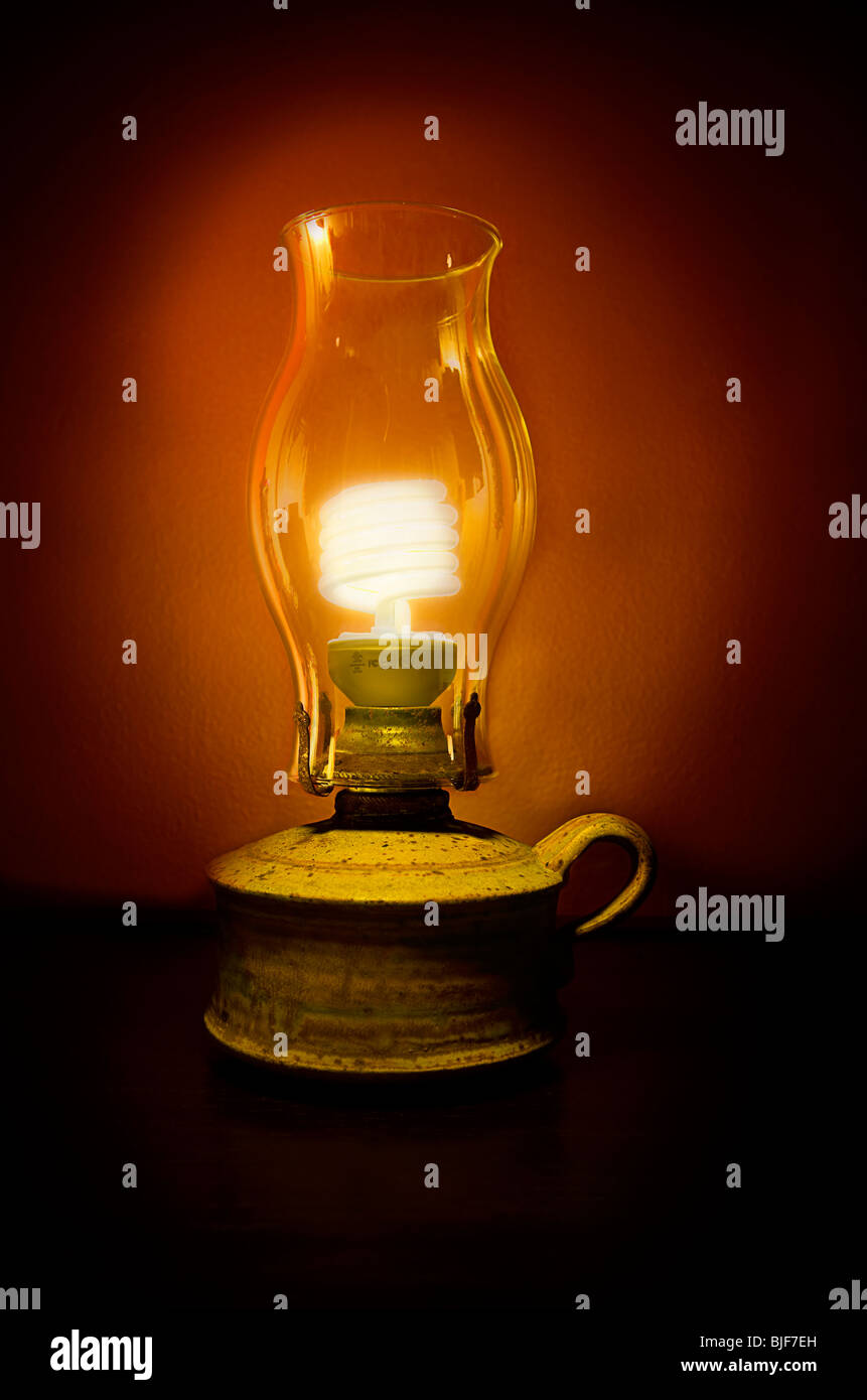 Energy saving sustainability light bulb in oil lamp - Stock Image