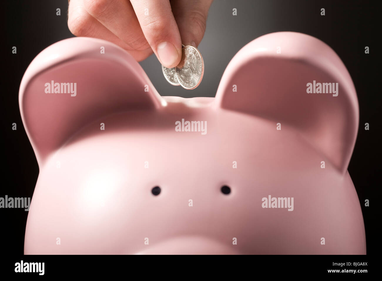 hand putting two quarters in a piggy bank - Stock Image