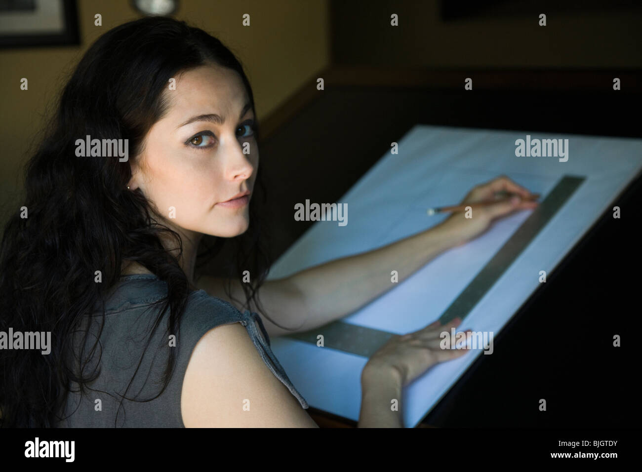 woman at a drafting table - Stock Image