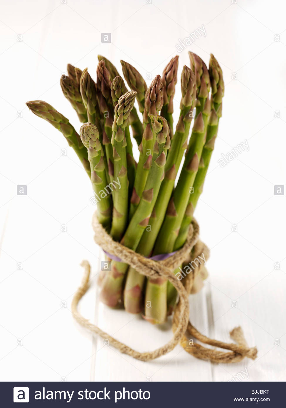 A bundle of green asparagus tied with string - Stock Image