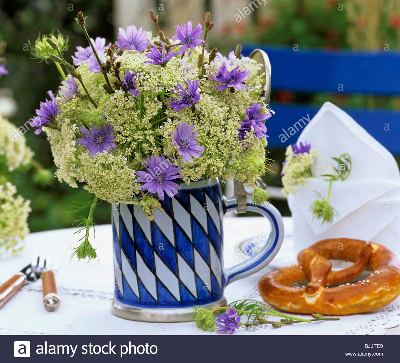 Chicory flowers & cow parsley in Bavarian beer mug, pretzel Stock ...