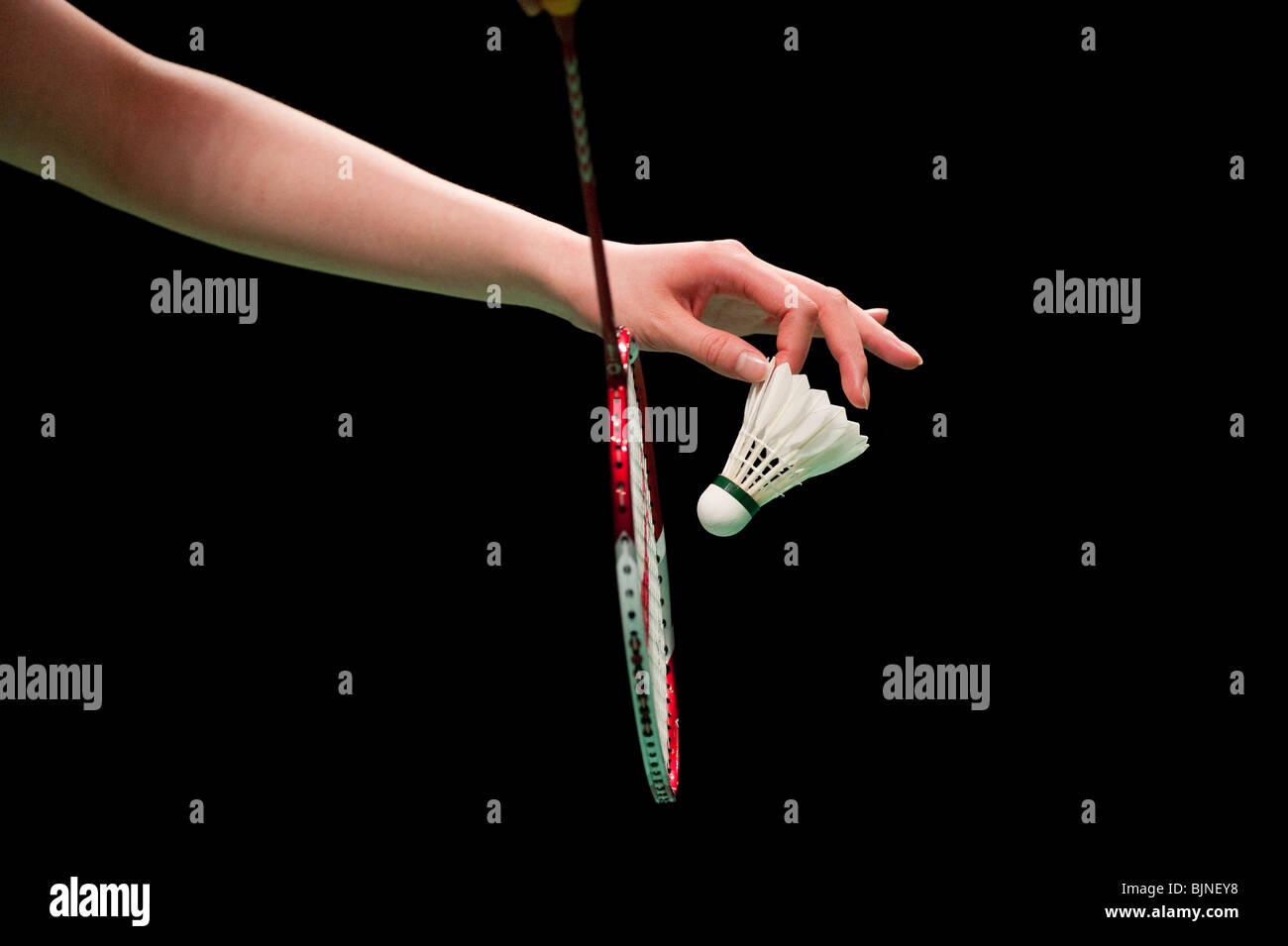 A badminton player prepares to serve a shuttlecock - Stock Image