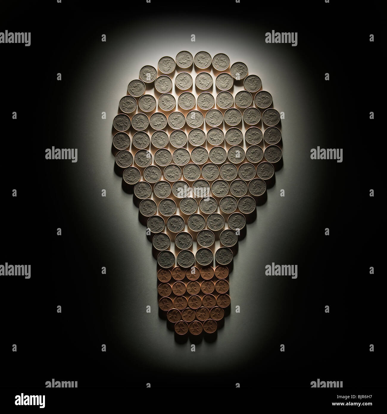 light bulb made out of dimes and pennies - Stock Image