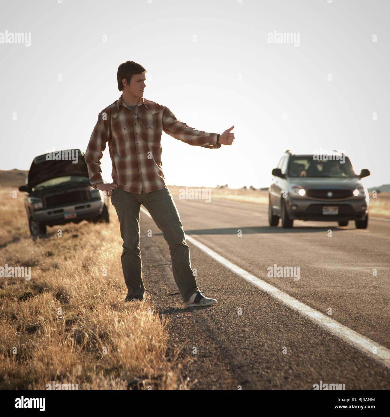 USA, Utah, man hailing on roadside, broken car in background - Stock Image