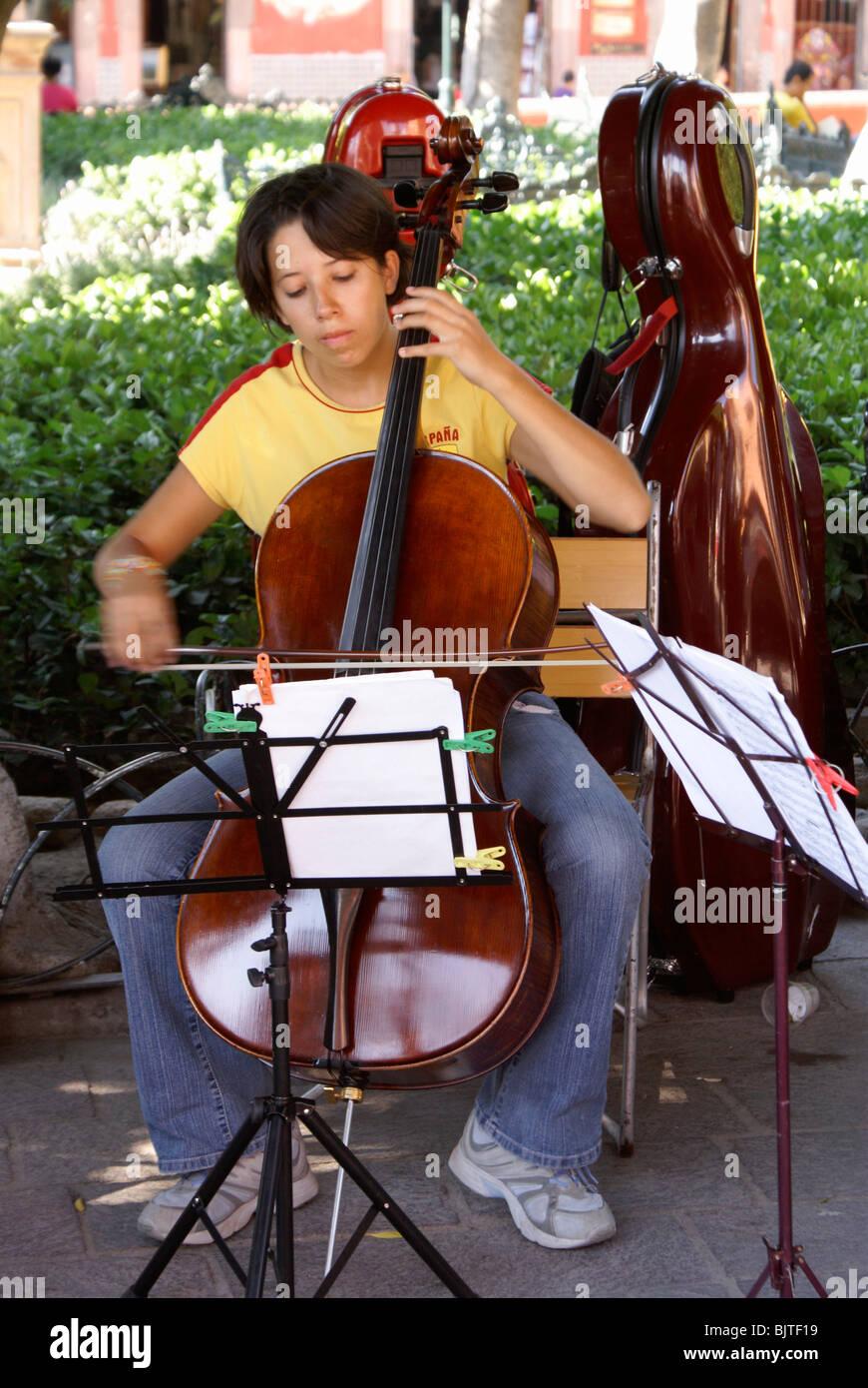Young female music student playing the cello in El Jardin, San Miguel de Allende, Guanajuato, Mexico - Stock Image