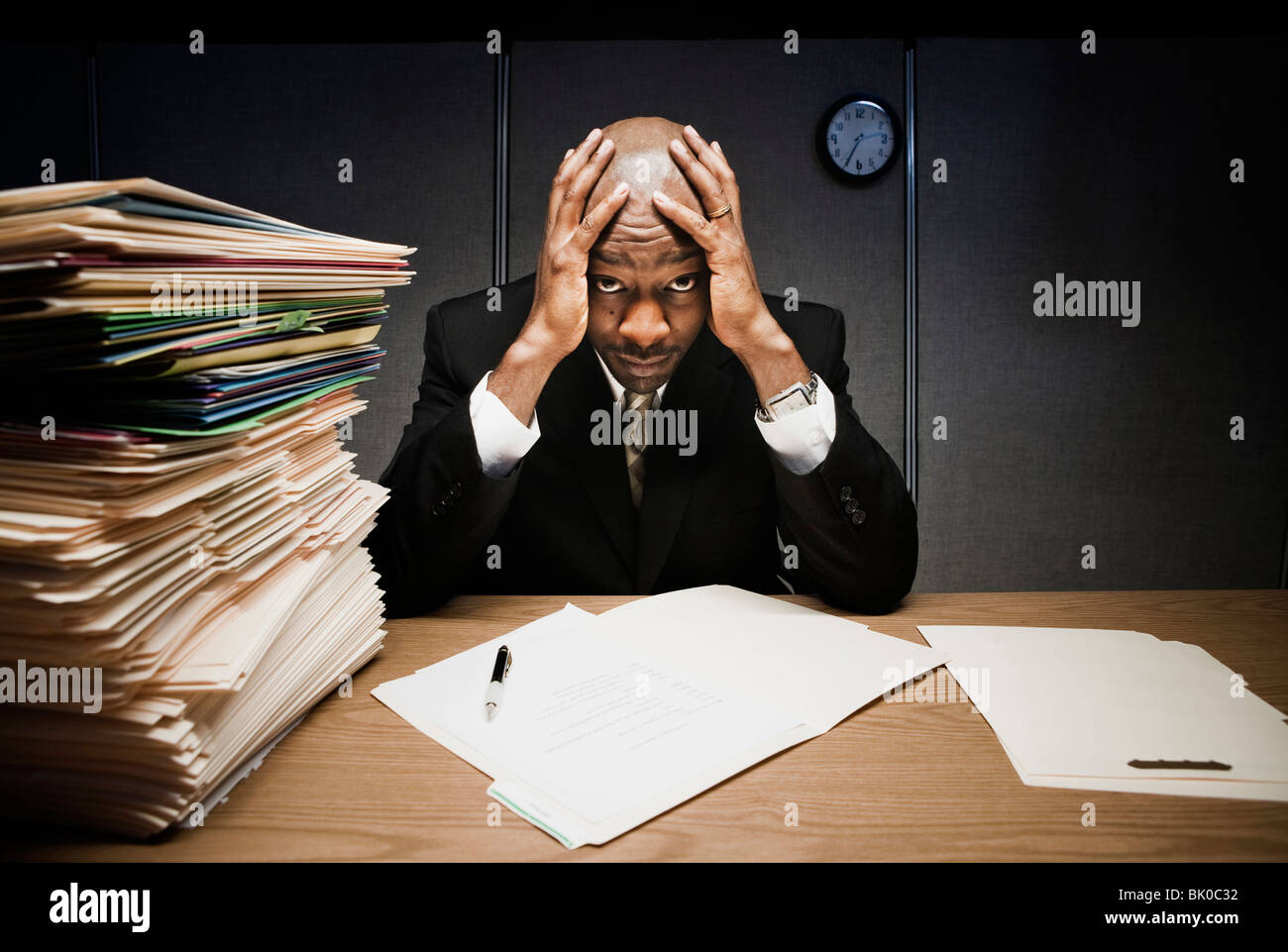 Businessman at desk with pile of folders - Stock Image