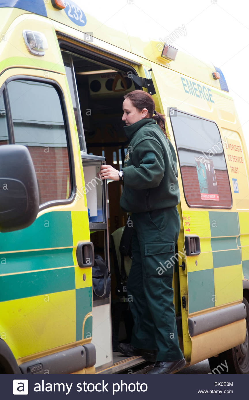 Woman paramedic stepping through side door of an ambulance. Female ambulance crew member in uniform, UK. - Stock Image