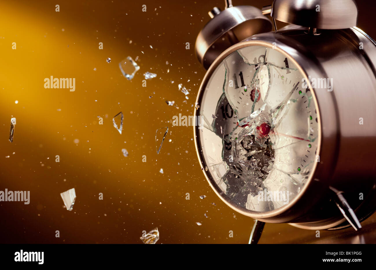 Alarm clock shattered by a bullet - Stock Image