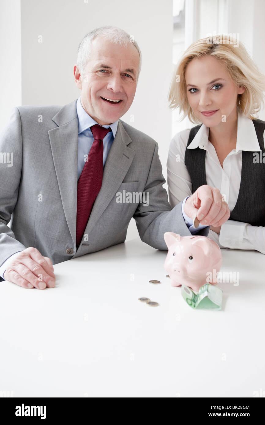 Man and woman saving money - Stock Image