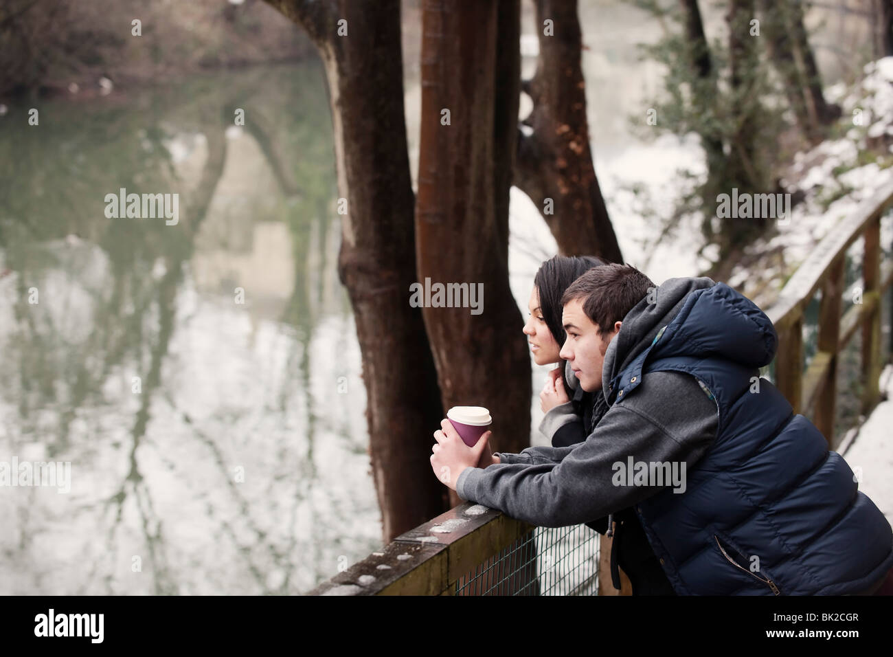 Couple relaxing by river in winter - Stock Image