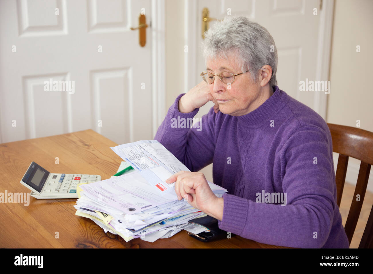 Elderly senior woman pensioner OAP lady retiree with a big pile of bills on the table looking depressed at a large Stock Photo
