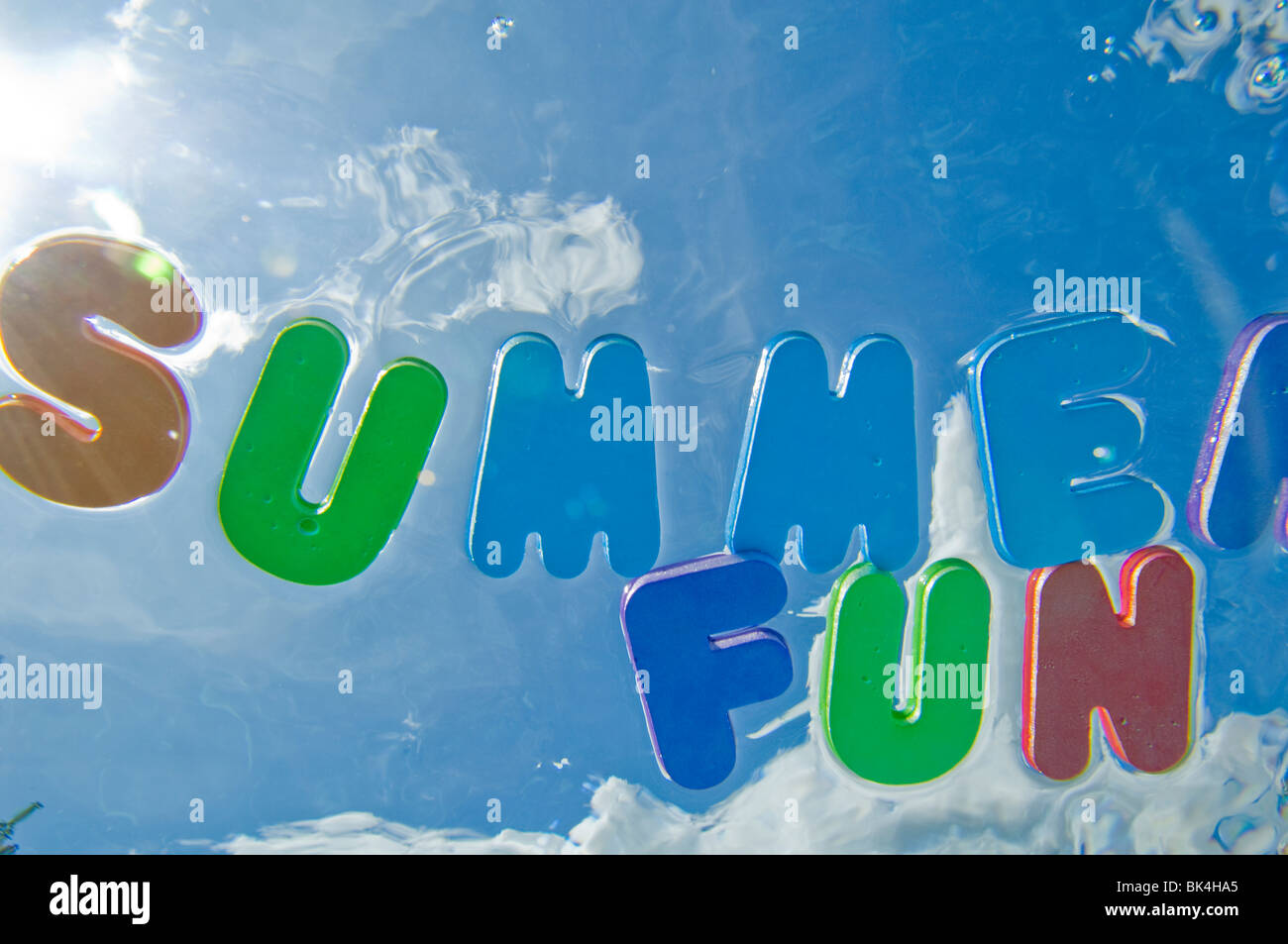Summer fun letters floating on swimming pool water - Stock Image